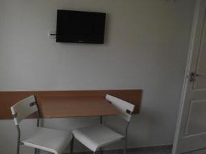 Apartmány u Františka - stolík s dvoma stoličkami a televízorom na steňe